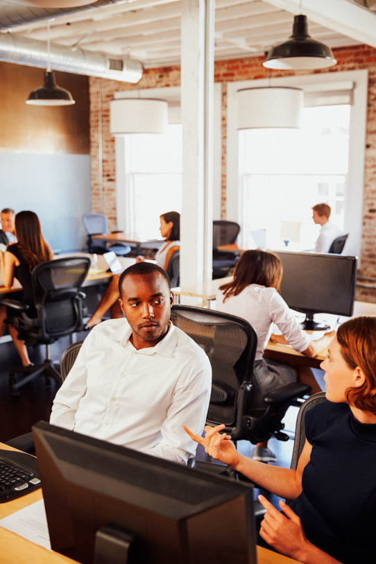 Businesspeople Working At Computers In Busy Modern Office